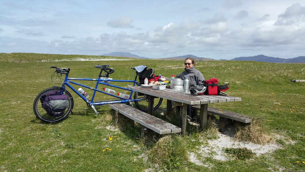Another photo of a windswept tandemist enjoying a picnic lunch, this time on the South Uist machair